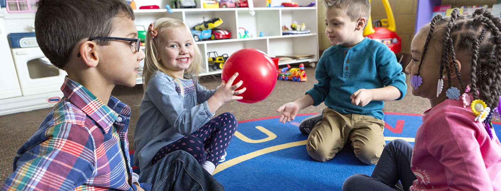 Children sitting on a classroom floor playing with a red bouncy ball