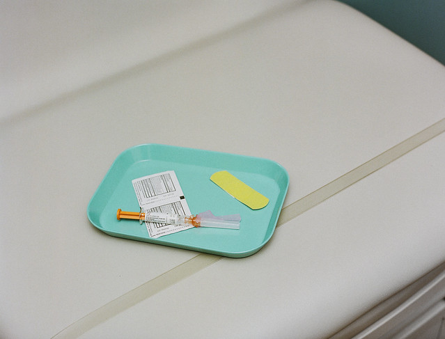 Vaccine on a tray with swabs and a band-aid