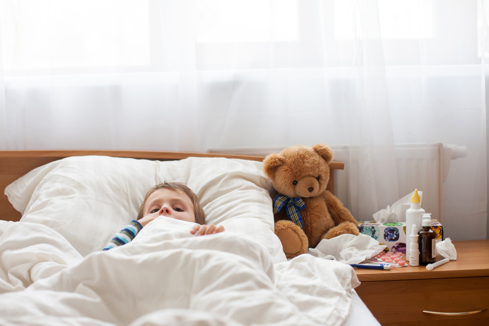 child sick with flu laying in bed with his teddy bear