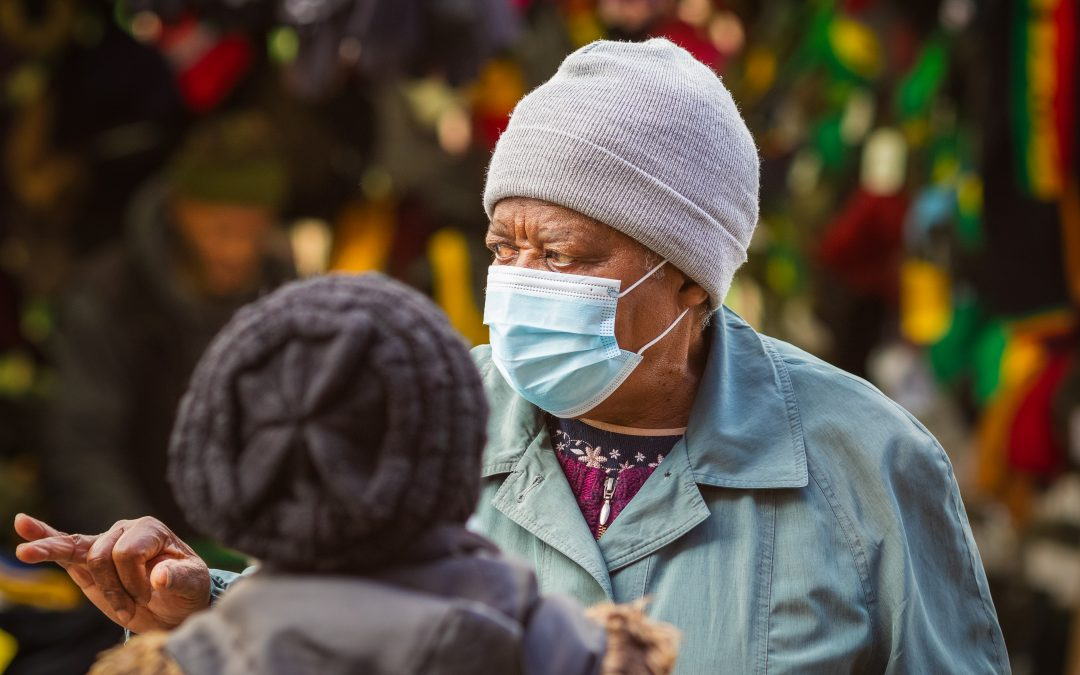 A senior black woman wearing a face mask while talking to her friend at Walthamstow market