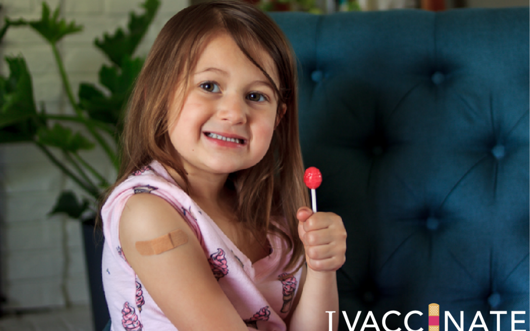 Young girl with bandaid on arm and lollipop